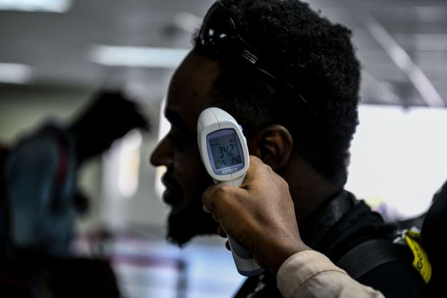 A Haitian health department employee scans the body temperature of incoming travellers at Port-au-Prince...