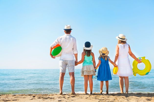 Young family with two children at beach. Holiday and travel concept