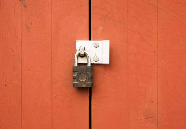 a metal padlock protecting locking two wooden doors outside;