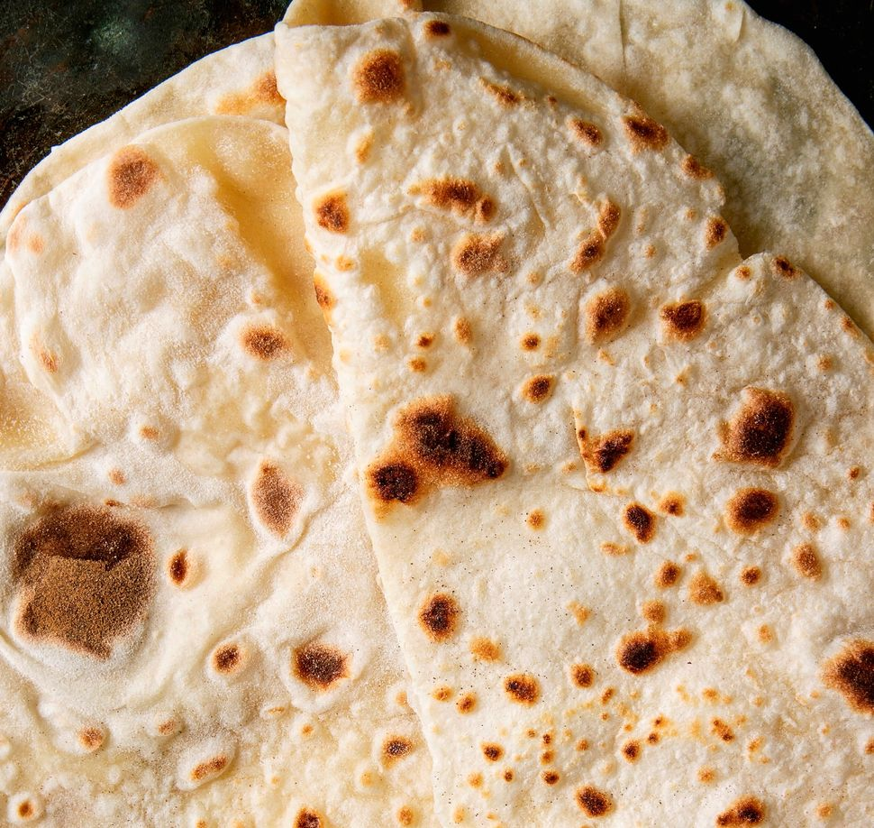 Homemade pita or chapati flatbread flapjack over dark metal background, Flat lay, close up. (Photo by: Natasha Breen/REDA&CO/Universal Images Group via Getty Images)