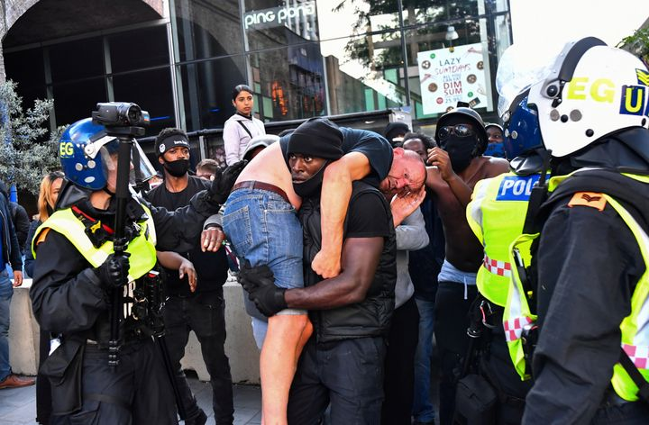 A protester carries an injured counter-protester to safety, near the Waterloo station during a Black Lives Matter protest fol