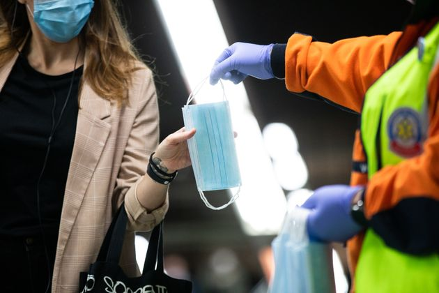 Un voluntario de protección civil entrega una mascarilla a una viajera en la estación de...