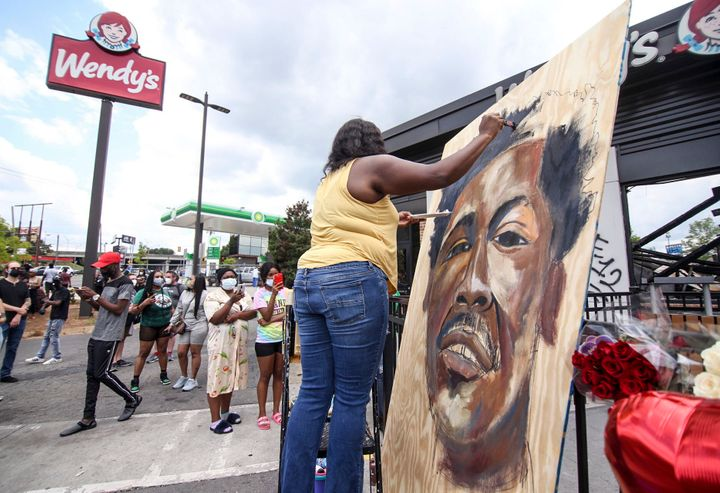 Ashley Dopson paints a picture of Rayshard Brooks in the parking lot of the Wendy's in Atlanta where Brooks, a 27-year-old bl