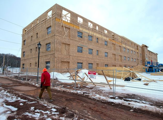 An unidentified man walks past an affordable housing complex, being constructed in Charlottetown on Feb....