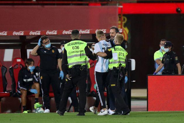 메시의 국가대표 유니폼을 입고 경기장에 난입한 팬을 보안 요원들이 끌어내고 있다. 2020. 6.