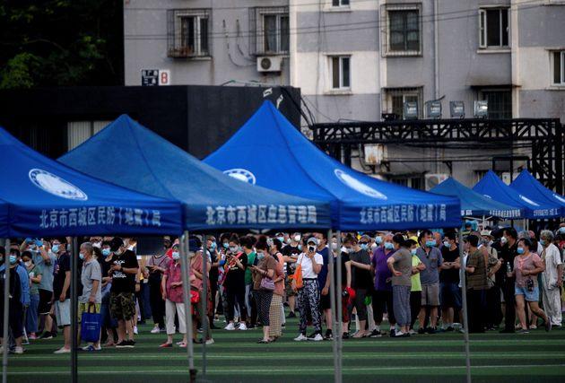 신파디 시장을 방문했거나 방문자와 접촉했을 것으로 의심되는 인근 주민들이 코로나19 진단검사를 받기 위해 줄을 서고 있다. 베이징, 중국. 2020년