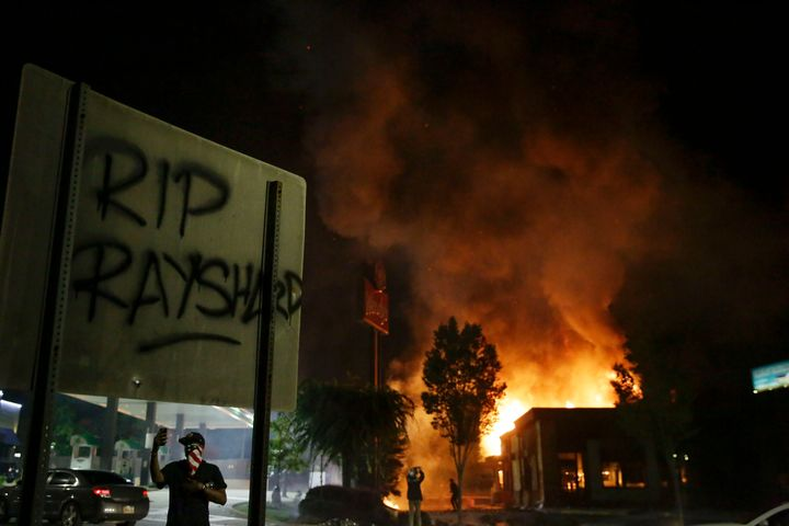"""RIP Rayshard"" is spray painted on a sign as as flames engulf a Wendy's restaurant during protests Saturday, June 13, 2020, i"