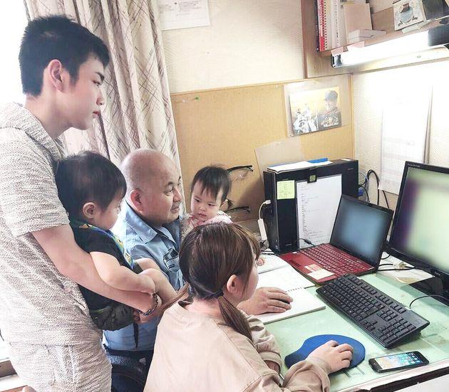 自宅でテレワークする渡邊さん。19歳の孫が授かった、生後11ヶ月のひ孫を抱っこしながら仕事をすることも。孫も、「じっちゃん、どうしたの?