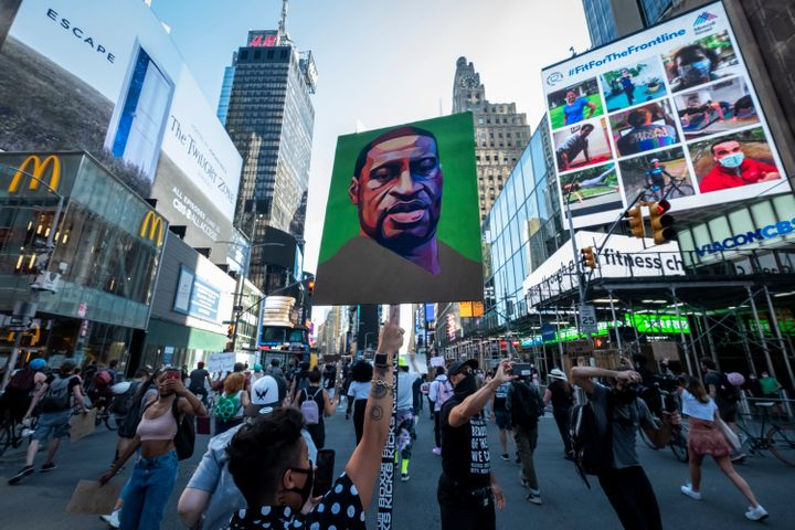 People protesting police brutality walk through Times Square with a portrait of George Floyd.