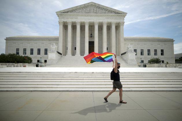 Ativista ergue bandeira do orgulho LGBT em frente ao prédio da Suprema Corte dos EUA após...