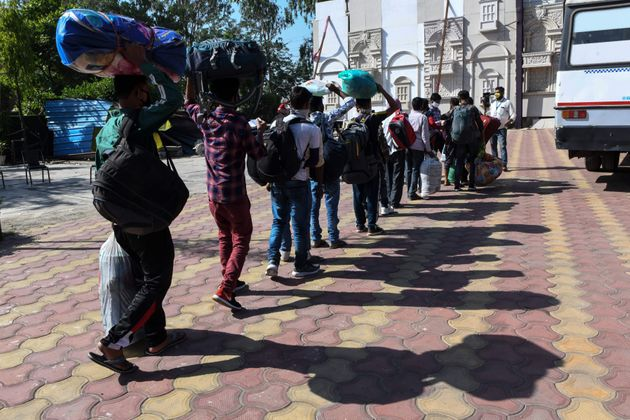 Migrant workers and their families line up toboard a bus to Amritsar railway station to take a...