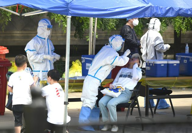 A health worker (2nd-L) wearing a protective suit takes a swab test on a woman in Beijing on June 16,...