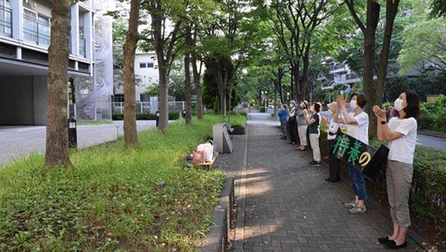 施設(左側)に拍手を送る地域住民ら(5月27日)