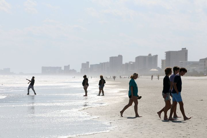 People walk along the shore as beaches reopen after closures aimed at preventing the spread of coronavirus disease (COVID-19)