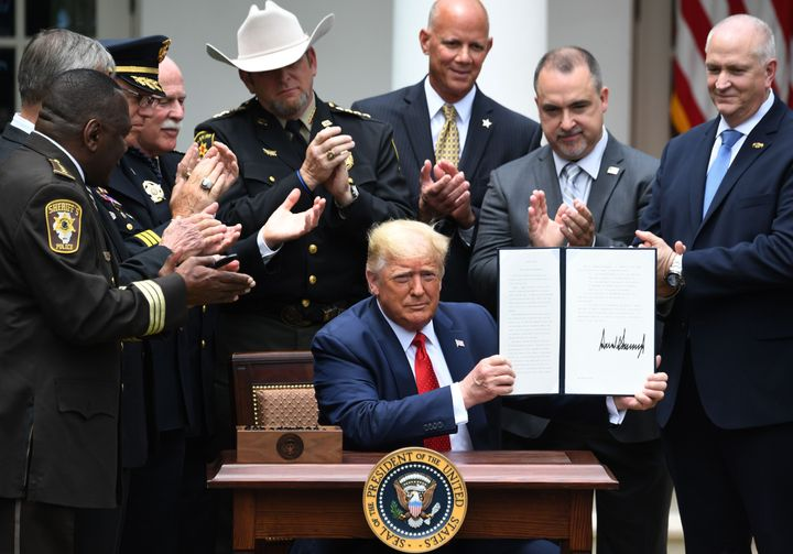 Surrounded by law enforcement officials, President Donald Trump shows his signature on an executive order on Safe Policing fo