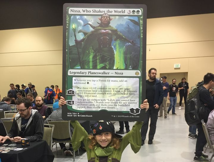 Dana holding up an oversized card showing Nissa, a legendary figure within the game.