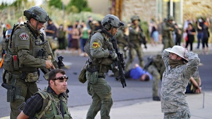 Albuquerque police detain members of the New Mexico Civil Guard, an armed civilian group, following the shooting of a man dur