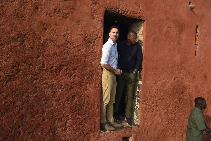 """Prime Minister Justin Trudeau speaks with Toronto Raptors president Masai Ujiri at the """"Door of the Journey of No Return"""" at the Goree Slave House during a visit to Senegal on Goree Island off the coast of Dakar on Feb. 12, 2020."""