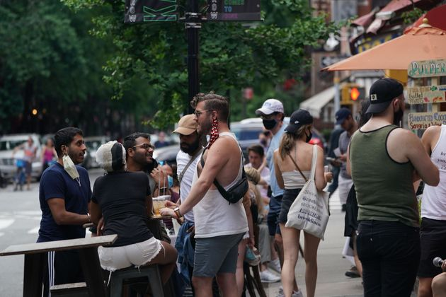 People drink outdoors at bars and restaurants in the Hells Kitchen neighborhood of New York on June 7,