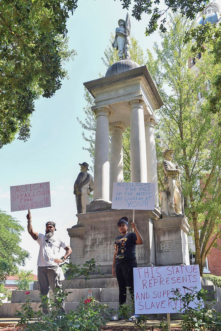 John Lewis, left, and Sonniah Ramirez, 12, protest for the removal of the Confederate monument that stands on the Lowndes Cou