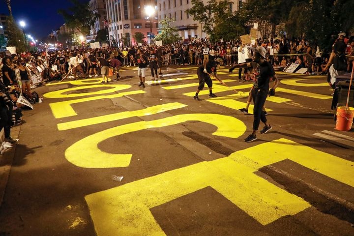 Demonstrators paint the words 'defund the police' as they protest June 6 near the White House in Washington, D.C., over the d