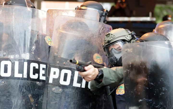A policeman shoots rubber bullets at protesters throwing rocks and water bottles during a demonstration next to the city of M