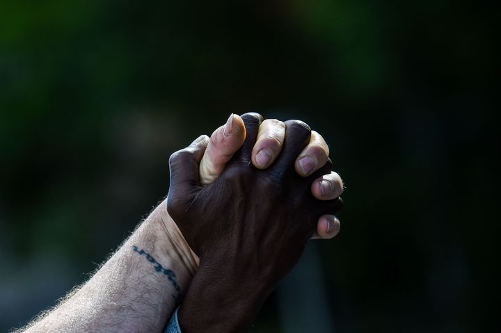 Men hold hands as they protest Rayshard Brooks' shooting death by police in a Wendy's restaurant parking lot on June 16, 2020, in Atlanta.