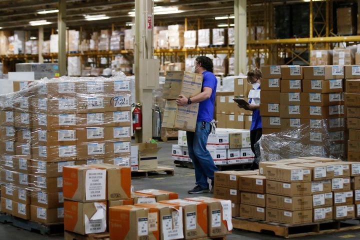 Workers carry boxes at Oklahoma's Strategic National Stockpile warehouse in Oklahoma City in April. States spent billions of
