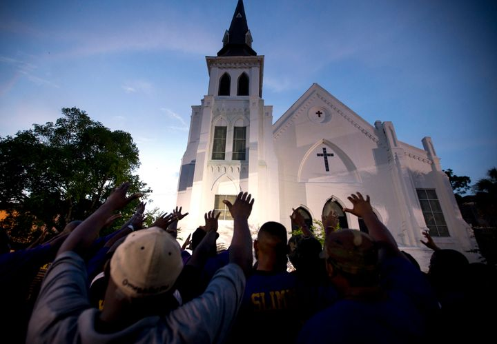 The men of Omega Psi Phi Fraternity Inc. lead a crowd of people in prayer outside the Emanuel AME Church in June 2015 after a