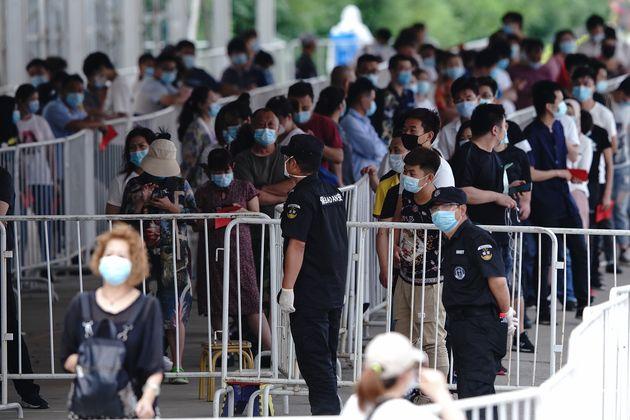Un gran número de personas que han estado en contacto con el mercado de Pekín esperan para...