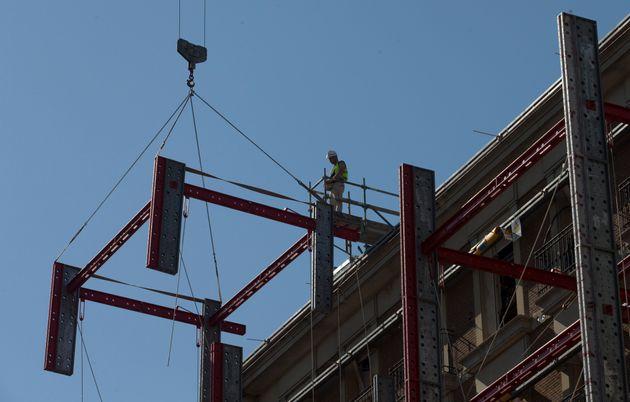 Un trabajador observa las labores de una grúa en un sitio en