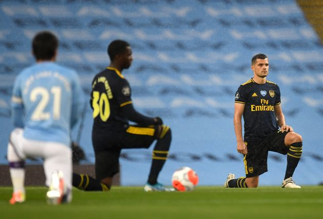 Granit Xhaka of Arsenal takes a knee in support of the Black Lives Matter movement prior to the Premier...