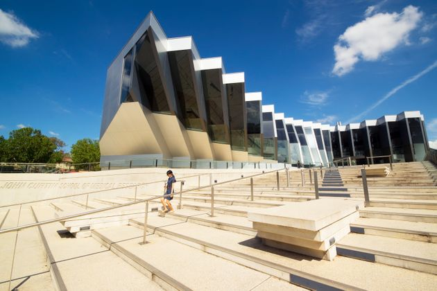 A woman walks down steps before the John Curtin School of Medical Research at the Australian National