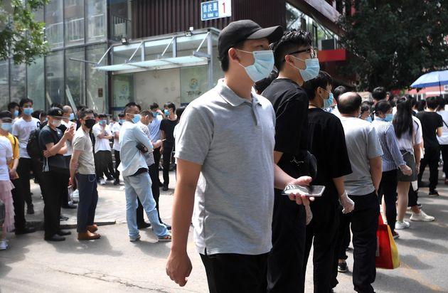 Des habitants de Pékin attendant de se faire dépister du Covid-19, le 18 juin