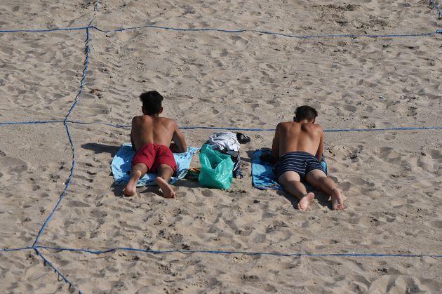 Dos jóvenes toman el sol en un área determinada en la playa de Poniente, en Benidorm