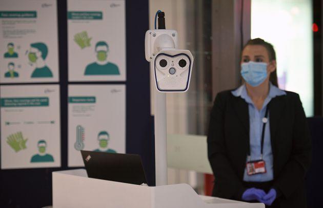 Una azafata, junto a un dispositivo de control de temperatura en el aeropuerto de Manchester (Reino