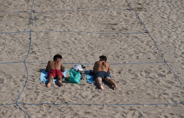 Two men sunbathe in their designated roped-off area on Poniente Beach in Benidorm, Spain, on June