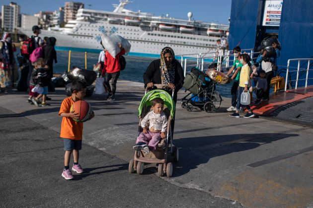 Refugees and migrants wearing masks arrive at the port of Piraeus , near Athens, on Thursday, June 11,...