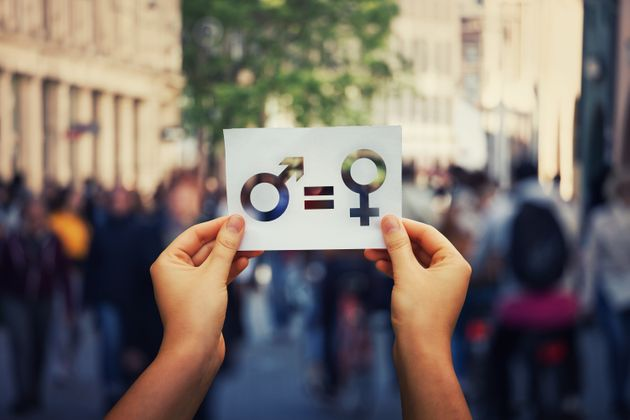 Gender equality concept as woman hands holding a white paper sheet with male and female symbol over a...