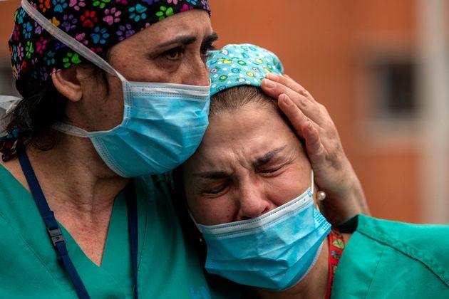 Empleadas médicas lloran durante un memorial por un compañero