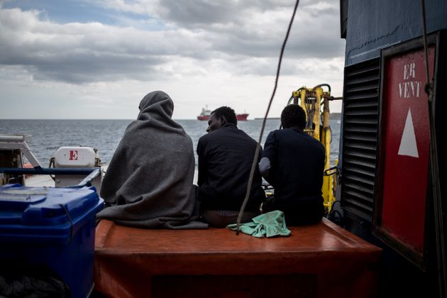 TOPSHOT - Three of the 47 rescued migrants aboard the Dutch-flagged Sea Watch 3 NGO vessel, sit on the...