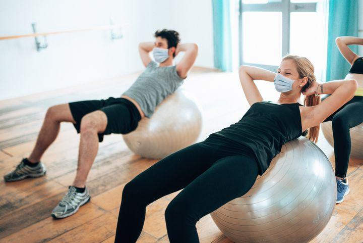 Un hombre y una mujer hacen ejercicio en un gimnasio.