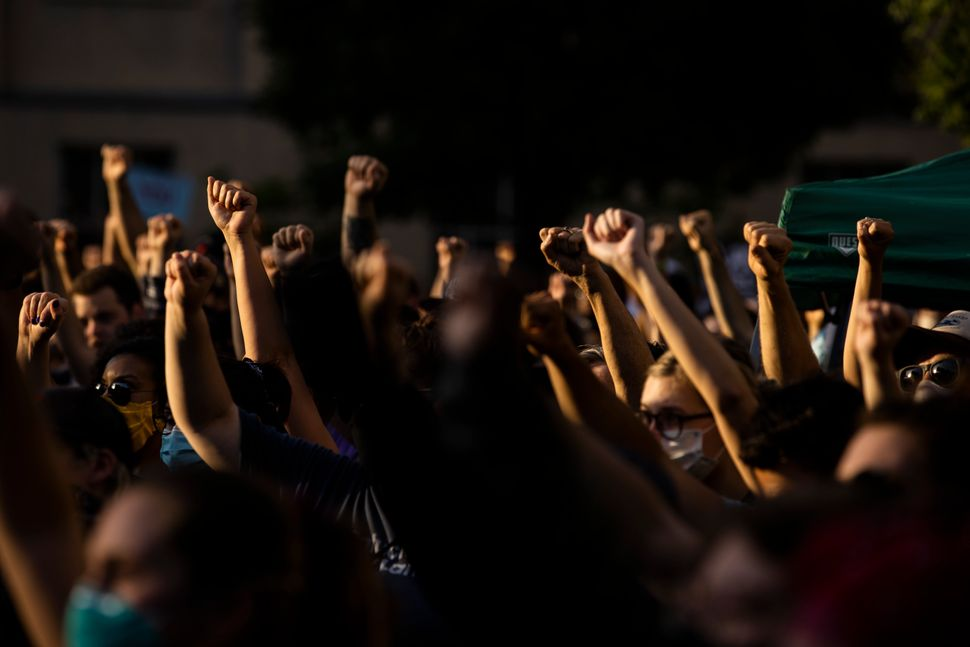 Protesters raise their fists in solidarity while listening to a speaker on June 5 in Louisville, Kentucky. Booker's presence