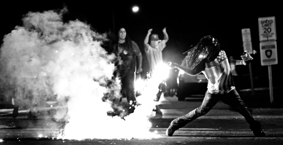 Edward Crawford Jr. returns a tear gas canister fired by police who were trying to disperse protesters in Ferguson, Missouri,