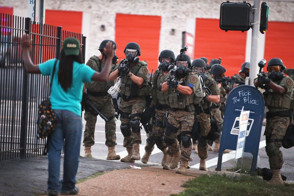 Police officers force protesters from the business district into nearby neighborhoods in Ferguson on Aug. 11, 2014.