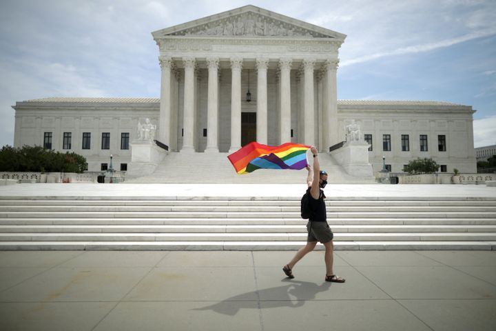 Joseph Fons, holding a Pride flag, walks in front of the U.S. Supreme Court building after the court ruled that LGBTQ people