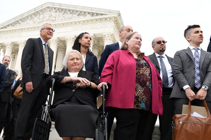 Aimee Stephens, seated, and her wife Donna Stephens, in pink, listen during a news conference outside the Supreme Court on Oc