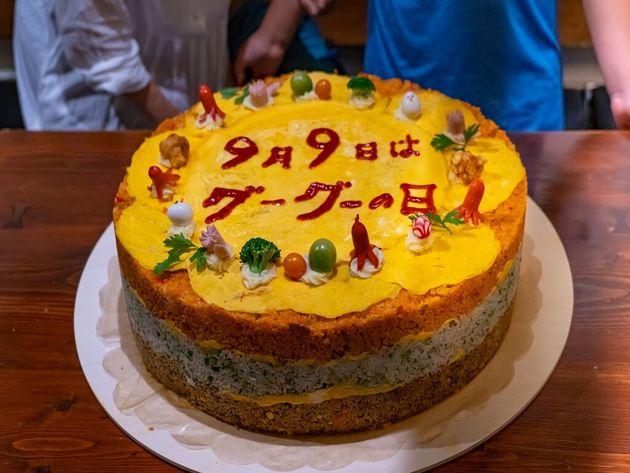 イベントの目玉、直径50cm、高さ11cmの「具ー具ーだくさんオムライスケーキ」!筆者考案、飯島奈美氏制作。みなと子ども食堂ボランティアの皆さまと。