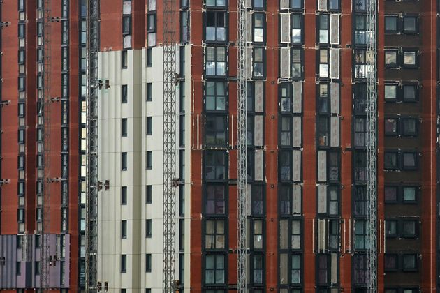A high-rise building is seen with cladding in the process of being