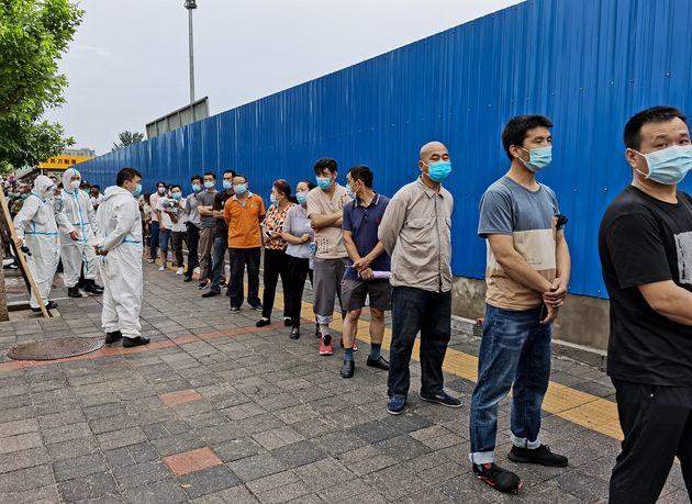 Ciudadanos que visitaron el mercado de Xinfadi esperan para realizarse test (Lintao Zhang/Getty